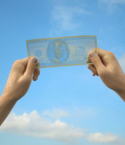 Hands holding transparent one hundred dollar bill up to sky