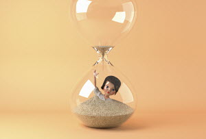 Businesswoman doll drowning in sand in hourglass