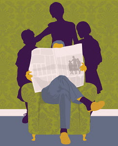 Family standing behind man reading newspaper in armchair