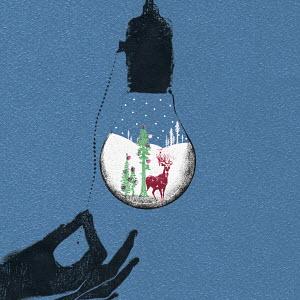 Hand turning on Christmas inside of light bulb