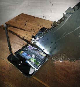 Chainsaw cutting through breaking smart phone on wooden table