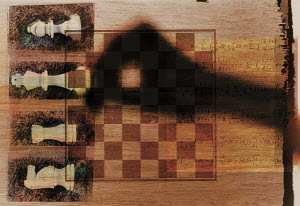 Hand moving piece on chess board with mathematical formulae