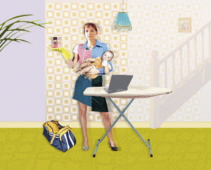 Mother with ironing board holding cell phone and baby