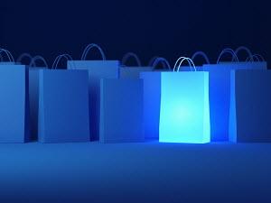 Glowing shopping bag among blue bags