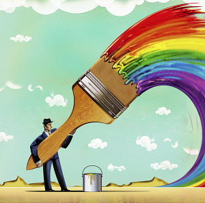 Businessman with large paintbrush painting multicolored rainbow
