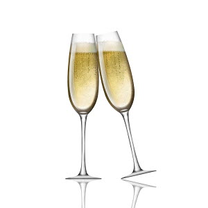Two champagne flutes toasting on white background