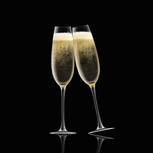 Two champagne flutes toasting on black background