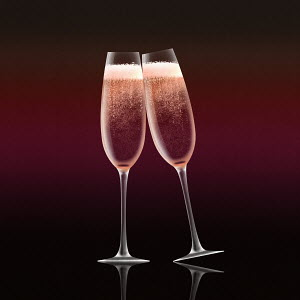 Pink champagne in flutes toasting on pink background