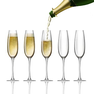 Champagne bottle pouring into flutes on white background