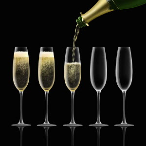 Champagne bottle pouring into flutes on black background