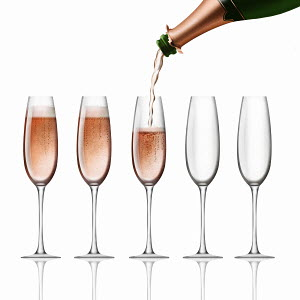 Bottle of pink champagne pouring into flutes on white background
