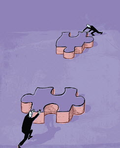 Businessmen pushing jigsaw pieces together