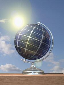 Sun shining on globe covered in solar panels