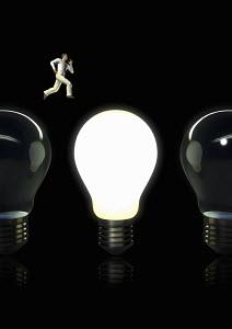 Businessman jumping from dark light bulb toward illuminated light bulb