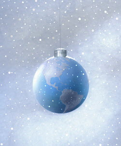 Snow falling around hanging globe Christmas ornament