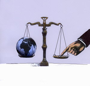 Businessman tipping scale opposite globe - Businessman tipping scale opposite globe
