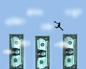 Businessman jumping across gaps between dollar banknotes
