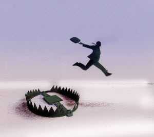 Businessman jumping over bear trap