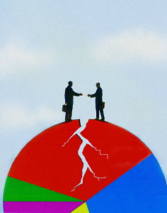 Businessmen shaking hands on cracking pie chart