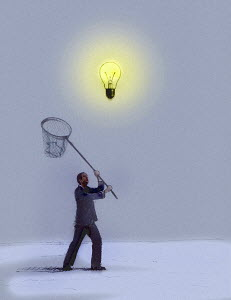 Businessman chasing hovering light bulb with net