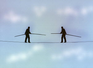 Men standing face to face on tightrope