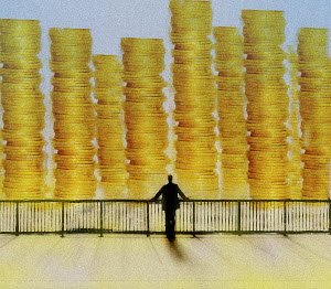 Businessman looking at large piles of money