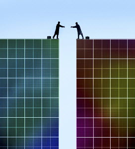 Businessmen reaching to shake hands across gap between two graph paper cliffs