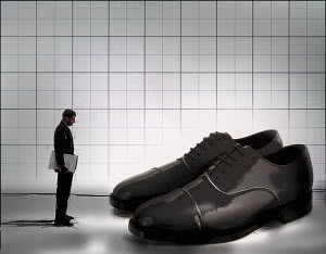 Ambitious businessman looking at large pair of empty shoes