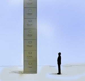 Businessman looking up at huge filing cabinet