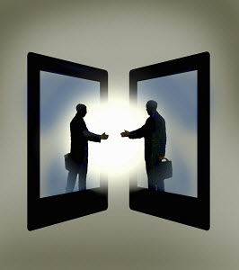 Two businessmen emerging from digital tablets reaching out to shake hands