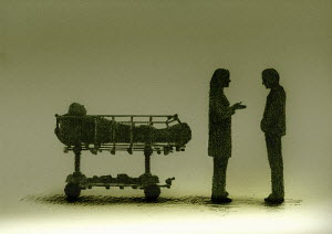 Doctor talking to relative about patient lying on hospital trolley bed