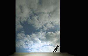 Man pushing large dark sliding door revealing blue sky