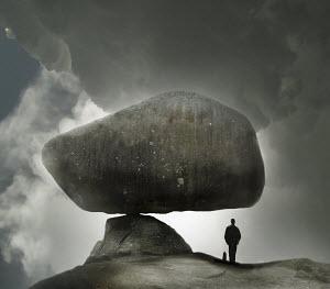 Oblivious businessman standing below ominous finely balanced large boulder - Oblivious businessman standing below ominous finely balanced large boulder