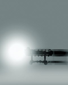 Patient on hospital trolley bed moving towards bright light