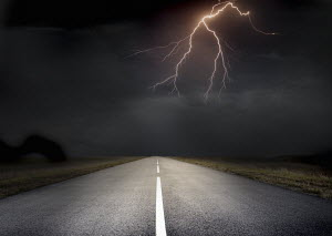 Forked lightning ahead above remote straight road - Forked lightning ahead above remote straight road