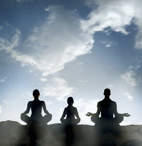Family silhouetted against blue sky sitting in lotus position meditating