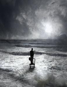 Businessman standing on chair in ocean waves - Businessman standing on chair in ocean waves