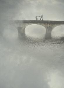 Two businessmen fighting over briefcase on bridge in fog