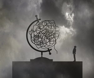Man looking up at tangled wire forming globe - Man looking up at tangled wire forming globe