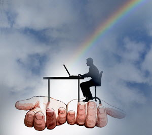 Businessman working at desk at the end of a rainbow supported by helping hands