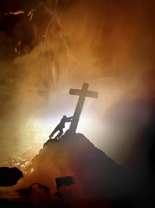 Man pushing over religious cross in burning hell