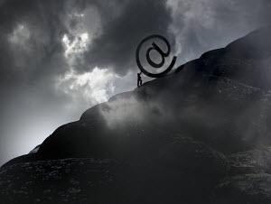 Businessman struggling to push large 'at' symbol uphill - Businessman struggling to push large 'at' symbol uphill