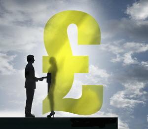 Businessman and businesswoman shaking hands behind transparent British pound sign