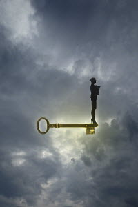 Confident businesswoman standing on top of gold key