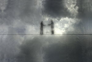Two businessmen reaching to shake hands on tightrope in fog