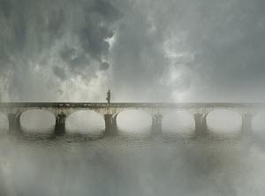 Businessman standing alone on bridge in fog - Businessman standing alone on bridge in fog