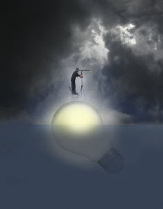 Man looking through telescope standing on top of illuminated light bulb floating in water