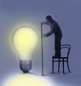 Businessman standing on chair measuring large illuminated light bulb