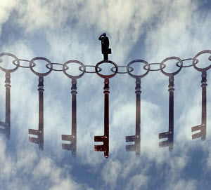 Businessman standing on top of chain of keys