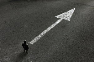 Man standing looking at arrow painted on road pointing the way ahead